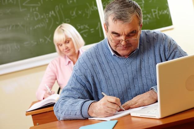 Gepensioneerde man met een bril huiswerk