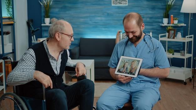 Gepensioneerde man met een handicap in gesprek met familie tijdens videogesprek