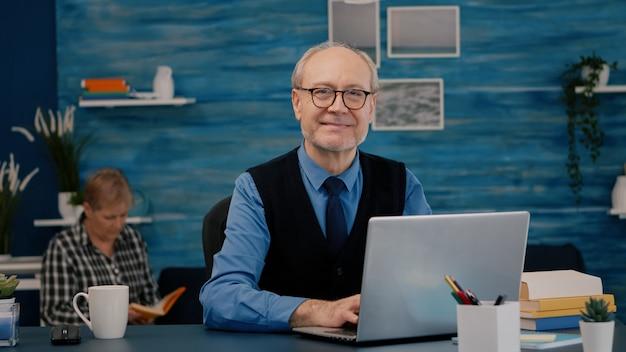 Gepensioneerde manager zit aan bureau voor camera glimlachend na het typen op laptop werken vanuit huis terwijl senior vrouw een boek op de achtergrond leest