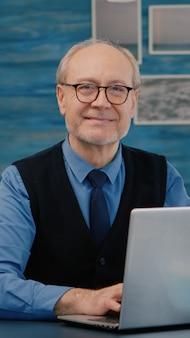 Gepensioneerde manager zit aan het bureau voor de camera en glimlacht na het typen op een laptop die vanuit huis werkt