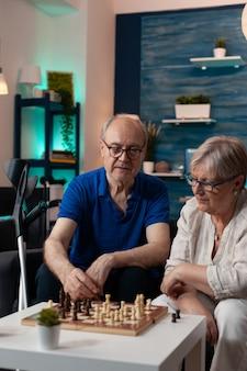 Gepensioneerde mensen die thuis op de bank in de woonkamer zitten terwijl ze aan boord een schaakspel spelen om te ontspannen. kaukasisch oud echtpaar geniet van leuke activiteiten binnenshuis, rustend op de bank met krukken