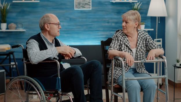 Gepensioneerde mensen met lichamelijke ziekte praten in verpleeghuis