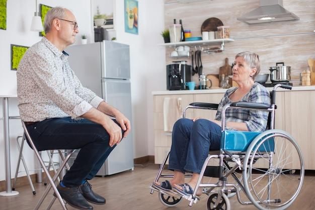 Gepensioneerde ongeldige vrouw in rolstoel die een gesprek heeft met oude bejaarde echtgenoot in keuken. oude man praten met vrouw. leven met een gehandicapte met een loophandicap