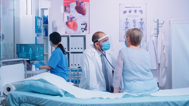 Gepensioneerde oude vrouw die een hartcontrole krijgt door cardioloog in beschermend vizier en een masker draagt. gezondheidszorg medische geneeskunde consultatie, met behulp van stethoscoop die professionele behandeling geeft aan zieke zieken