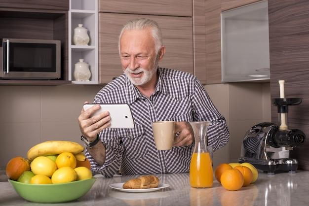 Gepensioneerde oudere man kijkt naar een video op een tablet en drinkt een kopje koffie in een keuken
