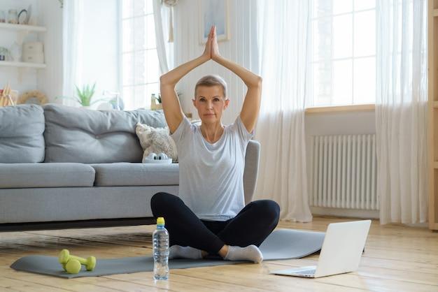 Gepensioneerde oudere vrouw geniet van persoonlijke vervulling yoga thuis wellness voor senioren