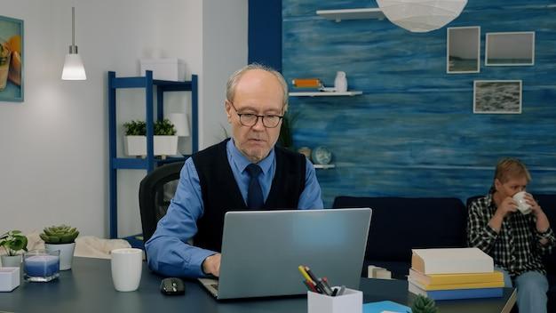 Gepensioneerde projectmanager die vanuit huis werkt, laptop opent die nieuws leest, financiële statistieken typt en analyseert, terwijl zijn vrouw thee drinkt op de achtergrond. oude man die moderne technologie gebruikt voor werk