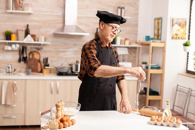 Gepensioneerde senior bakker met schort en bonete die ingrediënten gebruikt voor zelfgemaakte pizza