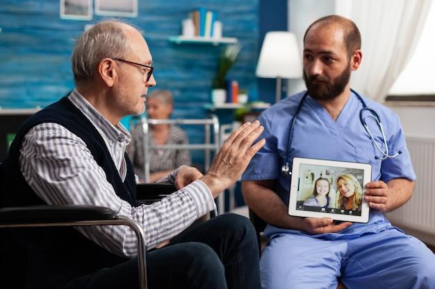 Gepensioneerde senior man begroet vrienden op afstand tijdens online videogesprek