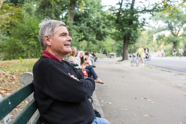 Gepensioneerde senior man bij park, zittend op een bankje