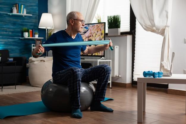 Gepensioneerde senior man zit op de zwitserse bal in de woonkamer en doet fitnessoefeningen in de gezondheidszorg