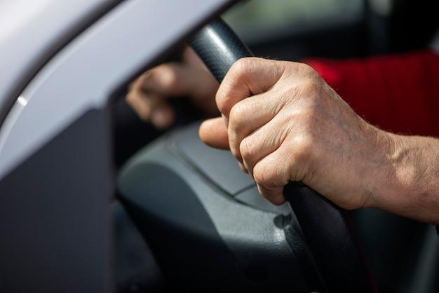 Gepensioneerde senior rijdende auto met handen op het stuur
