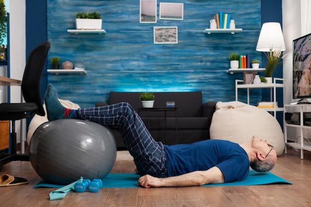Gepensioneerde senior sportman die op yogamat zit en oefeningen voor het opwarmen van de benen oefent met behulp van de zwitserse bal die de buikspieren uitrekt