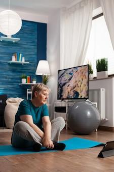 Gepensioneerde senior vrouw in sportkleding zittend op yoga mat kijken naar fitnessles op laptop