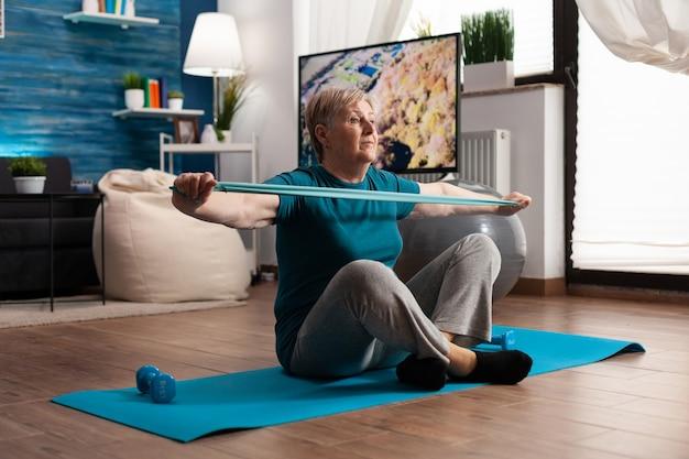 Gepensioneerde senior vrouw zittend op yoga mat in lotuspositie armen spieren uitrekken met behulp van elastische elastische band tijdens wellness sport routine in de woonkamer. gepensioneerde die lichaamsweerstand uitoefent