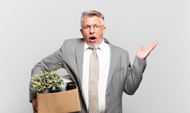 Gepensioneerde senior zakenman die verrast en geschokt kijkt, met open mond terwijl hij een object vasthoudt met een open hand aan de zijkant