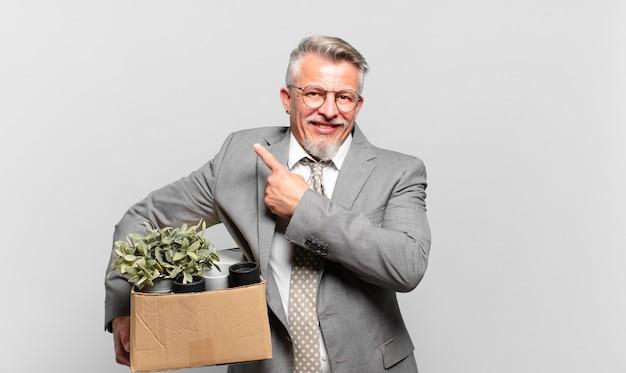 Gepensioneerde senior zakenman die vrolijk lacht, zich gelukkig voelt en naar de zijkant en naar boven wijst, een object in de kopieerruimte toont