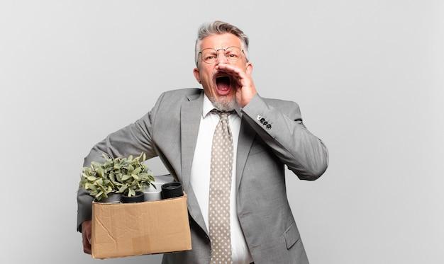 Gepensioneerde senior zakenman die zich gelukkig, opgewonden en positief voelt, een grote schreeuw geeft met de handen naast de mond, roept