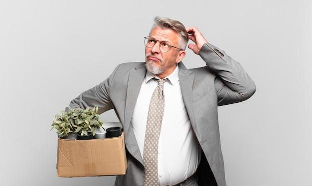 Gepensioneerde senior zakenman die zich verbaasd en verward voelt, hoofd krabt en opzij kijkt