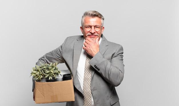 Gepensioneerde senior zakenman glimlachend met een gelukkige, zelfverzekerde uitdrukking met de hand op de kin, zich afvragend en opzij kijkend