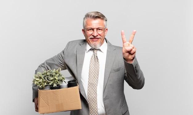 Gepensioneerde senior zakenman glimlacht en ziet er vriendelijk uit, toont nummer twee of seconde met de hand naar voren, aftellend
