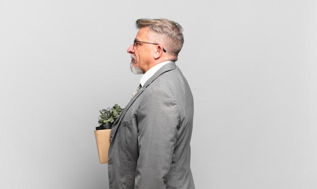Gepensioneerde senior zakenman op profielweergave die ruimte vooruit wil kopiëren, denken, fantaseren of dagdromen