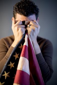 Gepensioneerde soldaat die zijn tranen schoonmaakt met de verenigde statenvlag