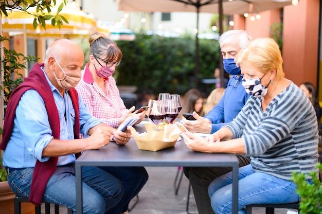 Gepensioneerde vrienden met gezichtsmasker kijken naar smartphone terwijl het drinken van rode wijn in restaurant
