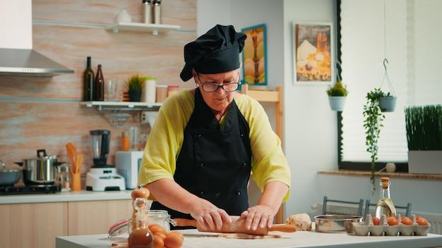 Gepensioneerde vrouw chef-kok met behulp van houten deegroller voor het koken van pizza. gelukkige bejaarde bakker met bonete die rauwe ingrediënten bereidt voor het bakken van traditionele pizzabestrooiing, zeven van bloem op tafel in de keuken.