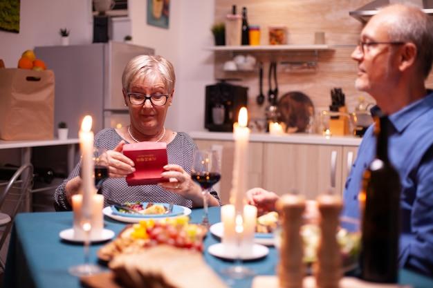 Gepensioneerde vrouw die een geschenkdoos van haar man vasthoudt tijdens het verjaardagsdiner van de relatie. gelukkig vrolijk bejaarde echtpaar dat samen thuis eet, van de maaltijd geniet, hun huwelijk viert, vakantie verras