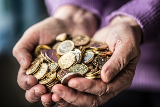 Gepensioneerde vrouw die euromunten in handen houdt. thema lage pensioenen.