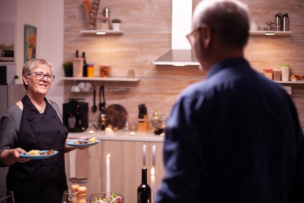 Gepensioneerde vrouw die lacht naar man en diner serveert in de keuken. bejaard oud echtpaar praten, aan tafel zitten in de keuken, genieten van de maaltijd, hun jubileum vieren met gezond eten.