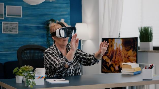Gepensioneerde vrouw die virtual reality ervaart met behulp van vr-headset in de woonkamer die vanuit huis werkt. oude externe werknemer zoekt, analyseert financiële rapporten terwijl oudere vrouw tv kijkt op de achtergrond