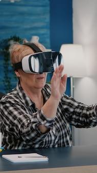 Gepensioneerde vrouw die virtual reality ervaart met behulp van vr-headset in de woonkamer die vanuit huis werkt