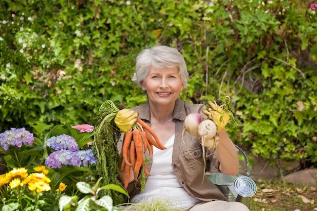 Gepensioneerde vrouw die werkt in de tuin