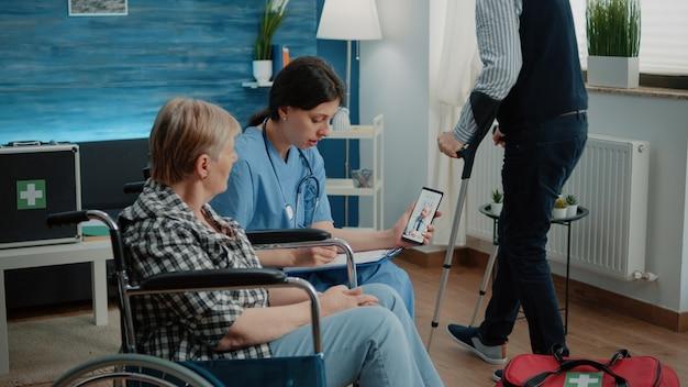 Gepensioneerde vrouw en verpleegster praten met arts tijdens videogesprek