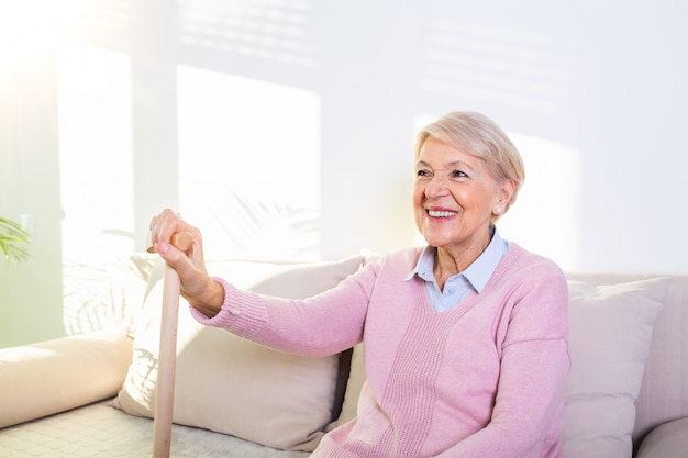 Gepensioneerde vrouw met haar houten wandelstok thuis. gelukkige hogere vrouw die thuis het houden van riet ontspannen en camera bekijken.