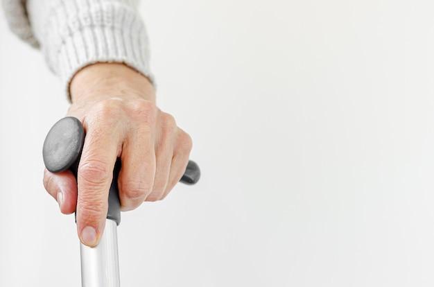 Gepensioneerde vrouw met metalen wandelstok in de hand. medisch en gezondheidszorgconcept. kopieer ruimte