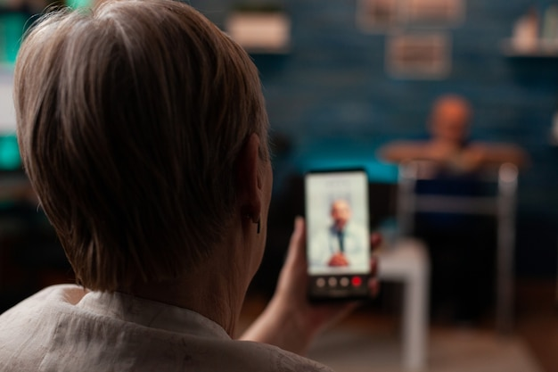 Gepensioneerde vrouw met smartphone met videogesprek