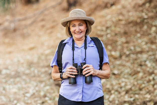 Gepensioneerde vrouw met verrekijker in het bos