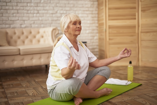 Gepensioneerde yogavrouw in lotus pose vrouwelijke gezondheid