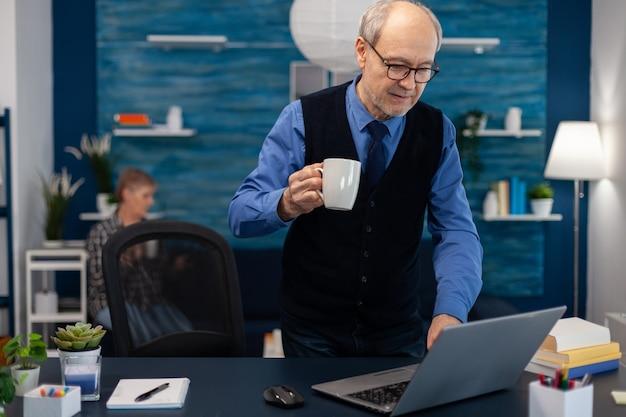 Gepensioneerde zakenman die laptop aanzet