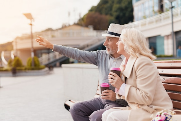 Gepensioneerden rusten in park. oude mensen houden koffie.