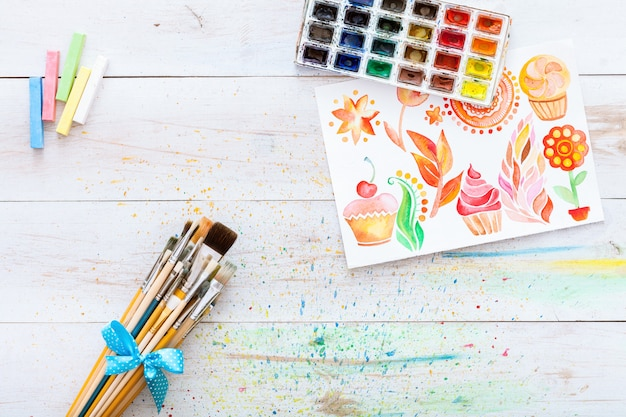 Geplaatste penselen en vakje met waterverven op witte houten lijst