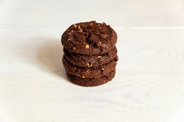 Geplakt van eigengemaakte amerikaanse chocoladekoekjes met noten op witte houten achtergrond. vers gebak.