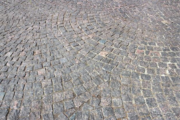 Geplaveide bestrating van grijs graniet close-up als achtergrond