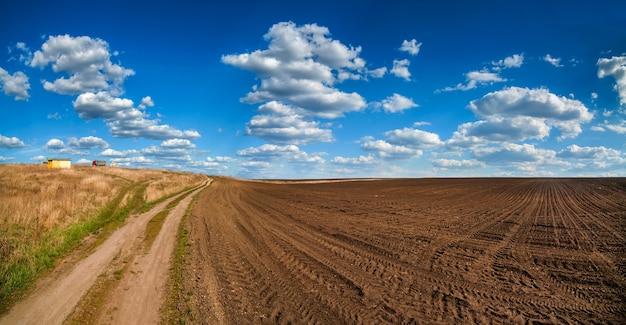Geploegd veld en onverharde weg in het voorjaar, mooie blauwe hemel met wolken