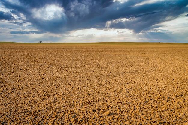 Geploegd veld met dramatische lucht op de achtergrond