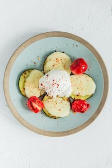 Gepocheerd ei met gebakken courgette, mozzarella kaas, tomaten en rode chili vlokken. bovenaanzicht.