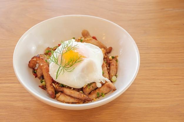 Gepocheerd ei met gegrilde varkensvlees nek rijst in witte plaat op houten tafel in restaurant.